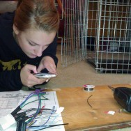 Aly takes a brake from soldering her new stereo to conduct important teen business via text.